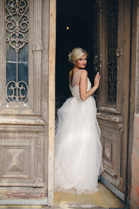 bride standing in front of the old door