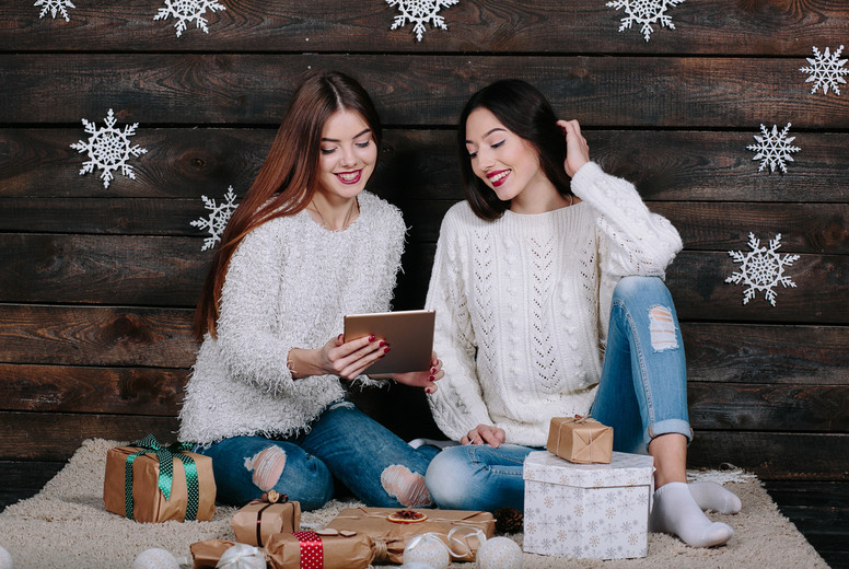 Two beautiful girls with a tablet  between gifts