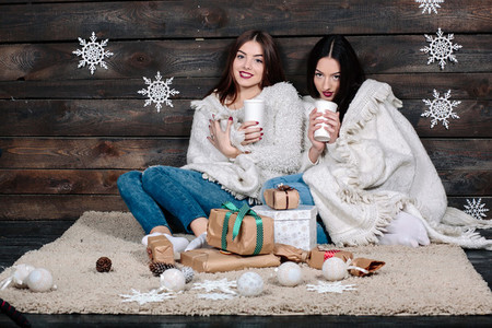 two girls drinking hot beverage