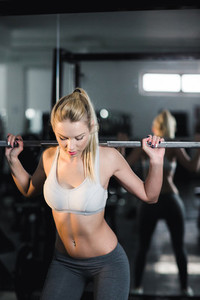 Girl doing exercise with barbell in gym