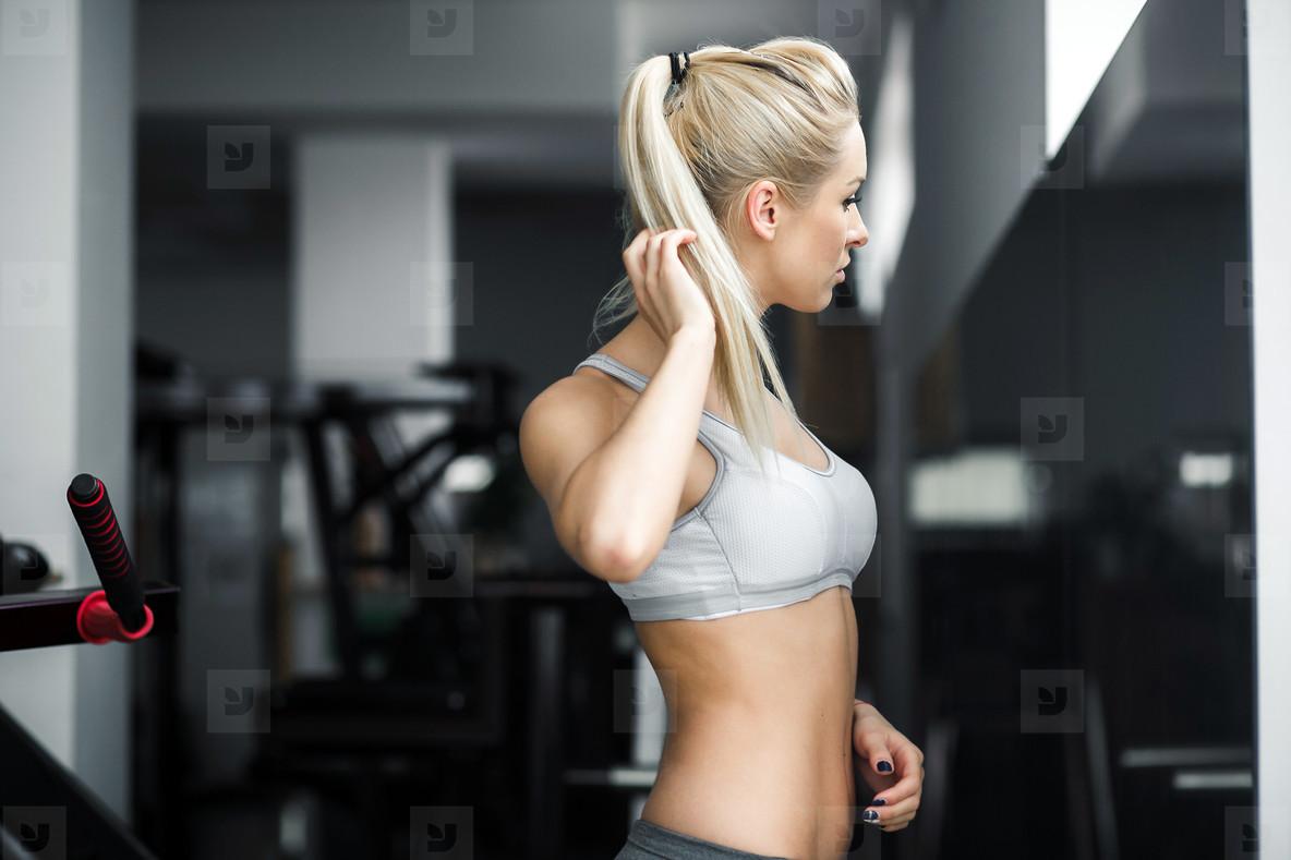 Beautiful girl watching in mirron in the gym