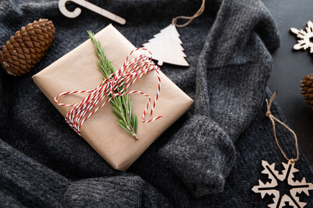 Christmas or winter time still life with gift box and wooden toys on a woolen sweather