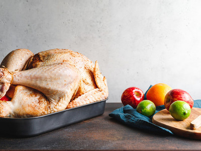 Raw whole turkey with fruits for stuffing on a kitchen table preparing Thanksgiving or Christmas recipe