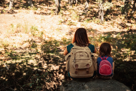 Mother and daughter seating together on a stone in the forest
