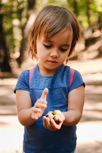 Little blonde girl with acorns in her hand in the forest path
