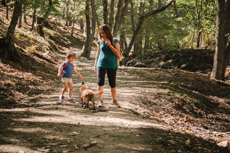 Mother and daughter walking trough a path in the woods