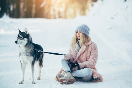 Beautiful girl with dog Husky in snowy woods