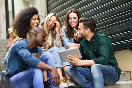 Multi ethnic group of young people looking at a tablet computer