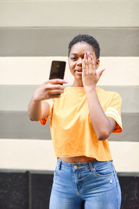 Young black woman taking selfie photographs with funny expression outdoors