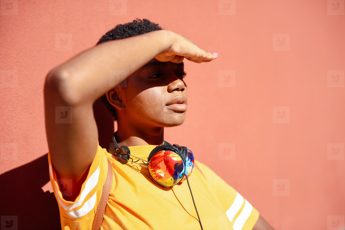 Young black woman covering with her hand the sun that falls on her eyes