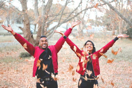 Couple throwing autumn leaves