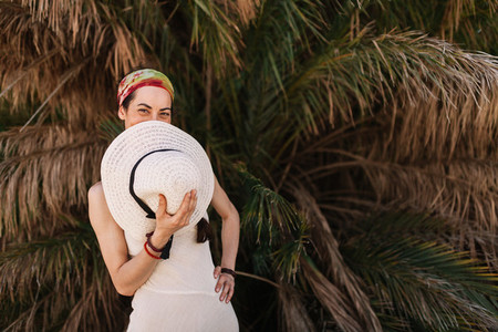 Woman wearing dress standing close to palm tree covers her mouth