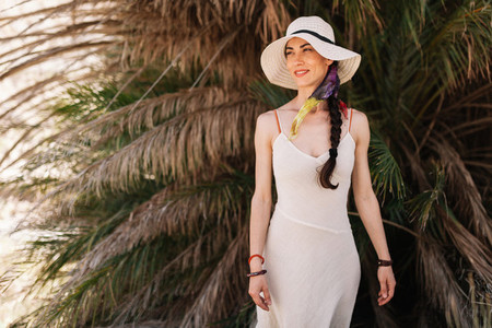 Smiling woman wearing dress standing close to palm tree