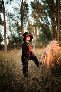 Boy disguised to halloween in the forest supported on a log