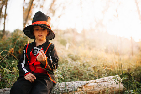 Boy disguised to halloween in the forest with blackberries