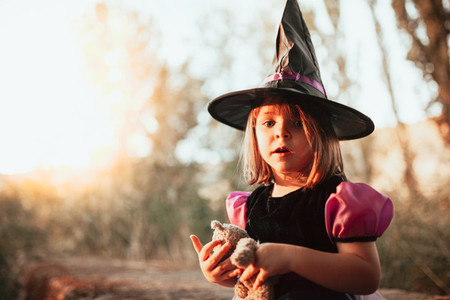 Girl standing disguised as a witch in the woods during Halloween