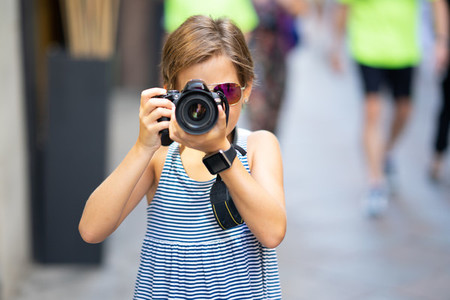 Little girl making photo with DSLR camera on city street
