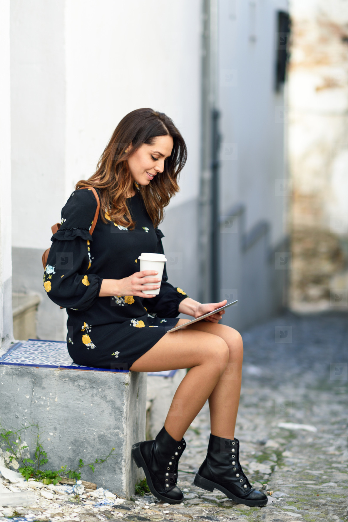 Middle aged young woman using digital tablet outdoors
