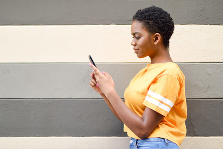 Young black woman using her smart phone outdoors