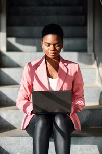 Black woman sitting on urban steps working with a laptop computer
