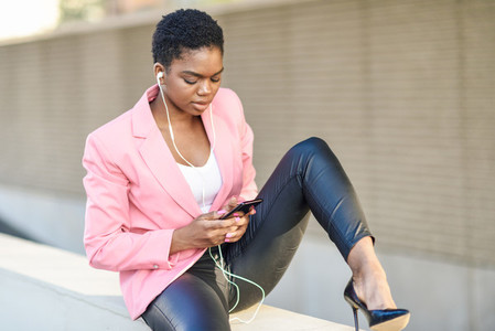 Black businesswoman sitting outdoors using smartphone with earphones