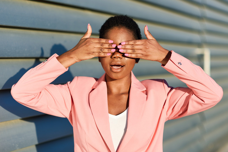 Funny black woman standing on urban wall covering her eyes with her hands