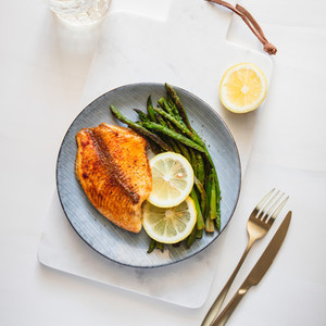 Roasted tilapia fish with asparagus on a white marble tray  Healthy mediterranean diet lunch or dinner  Top view  flat lay