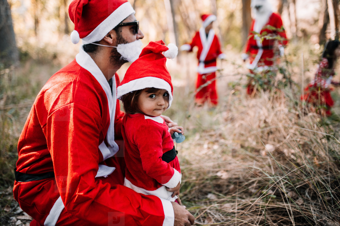 Father and daughter disguised to christmas on the forest