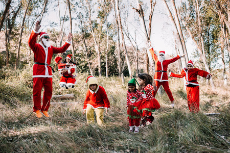 Group of people disguised to christmas jumping on the forest