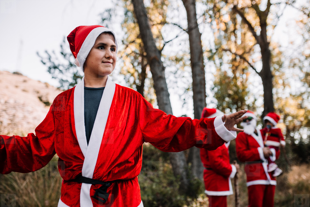 Boy disguised to christmas on the forest with his family