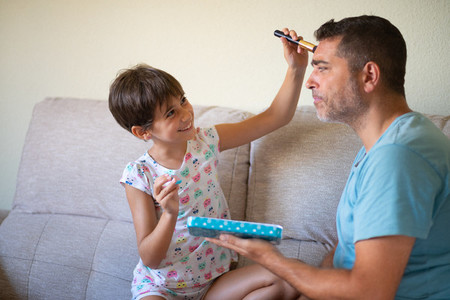 Little cute daughter doing make up to her father