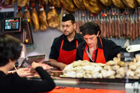 Butchers attending a customer in a butchers shop