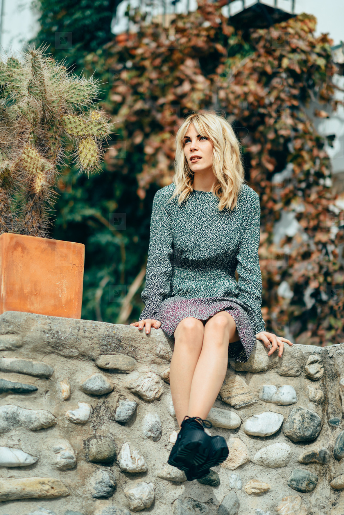 Happy young blond woman sitting on urban autumn background
