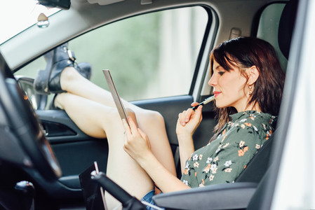 Woman writing in a notebook with a pen in a white car