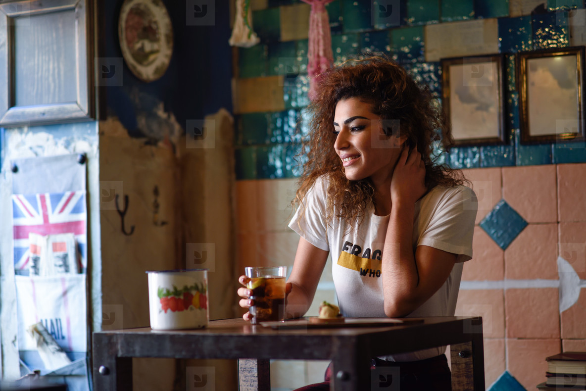 Arabic woman in a beautiful bar looking through the window