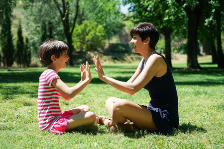 Mother and daughter playing with hands in city park