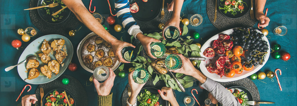Company of friends gathering for Christmas dinner  wide composition