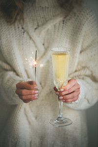 Woman in sweater holding champagne and sparkler in hands close up