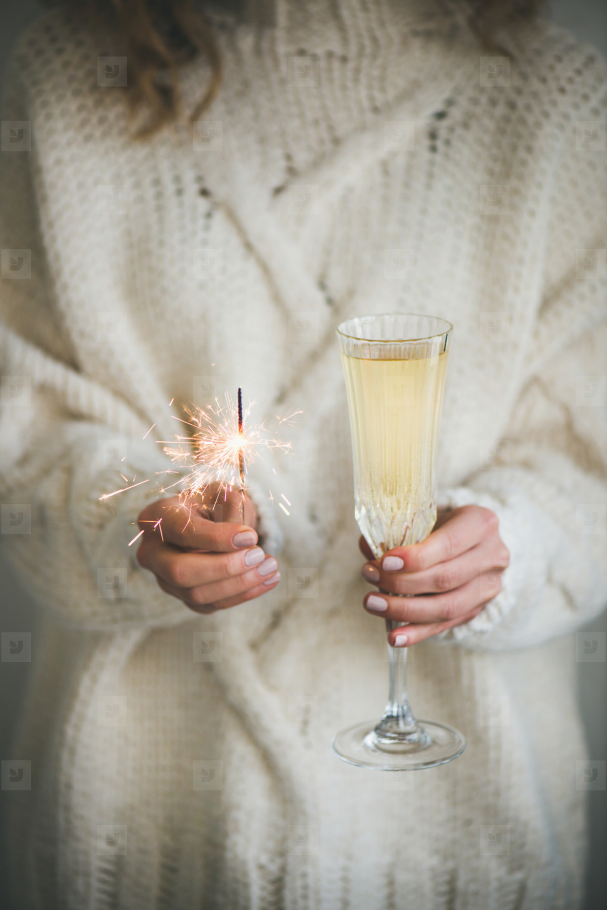 Woman in sweater holding champagne and sparkler in hands