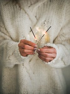 Woman in sweater holding Christmas sparklers in hands close up
