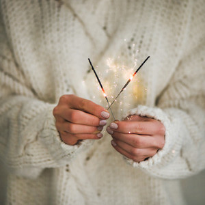 Woman in sweater holding Christmas sparklers in hands  square crop