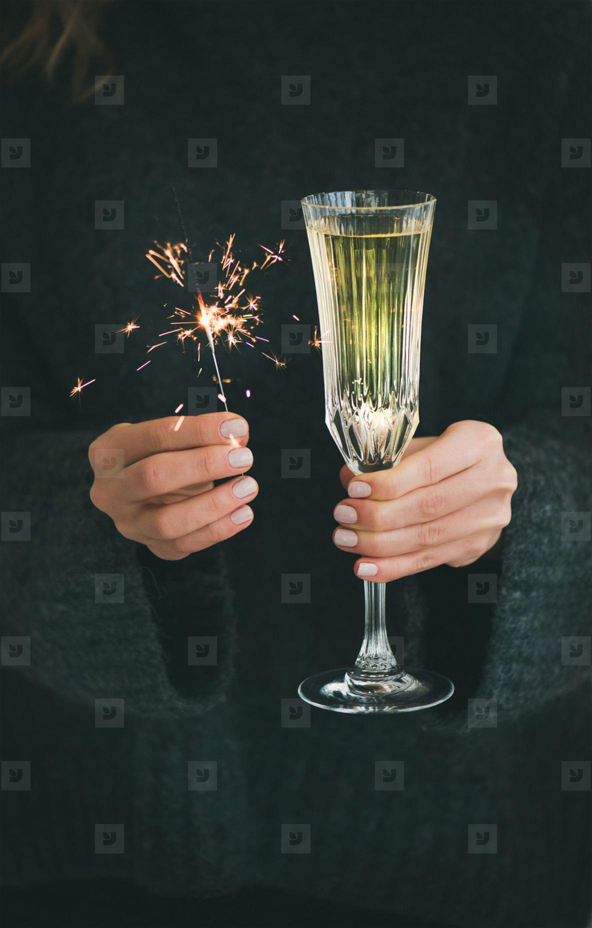 Woman in grey sweater holding sparklers and glass of champagne