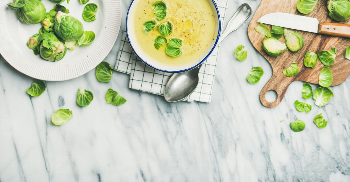 Brussels sprouts vegetable cream soup in bowl over marble background