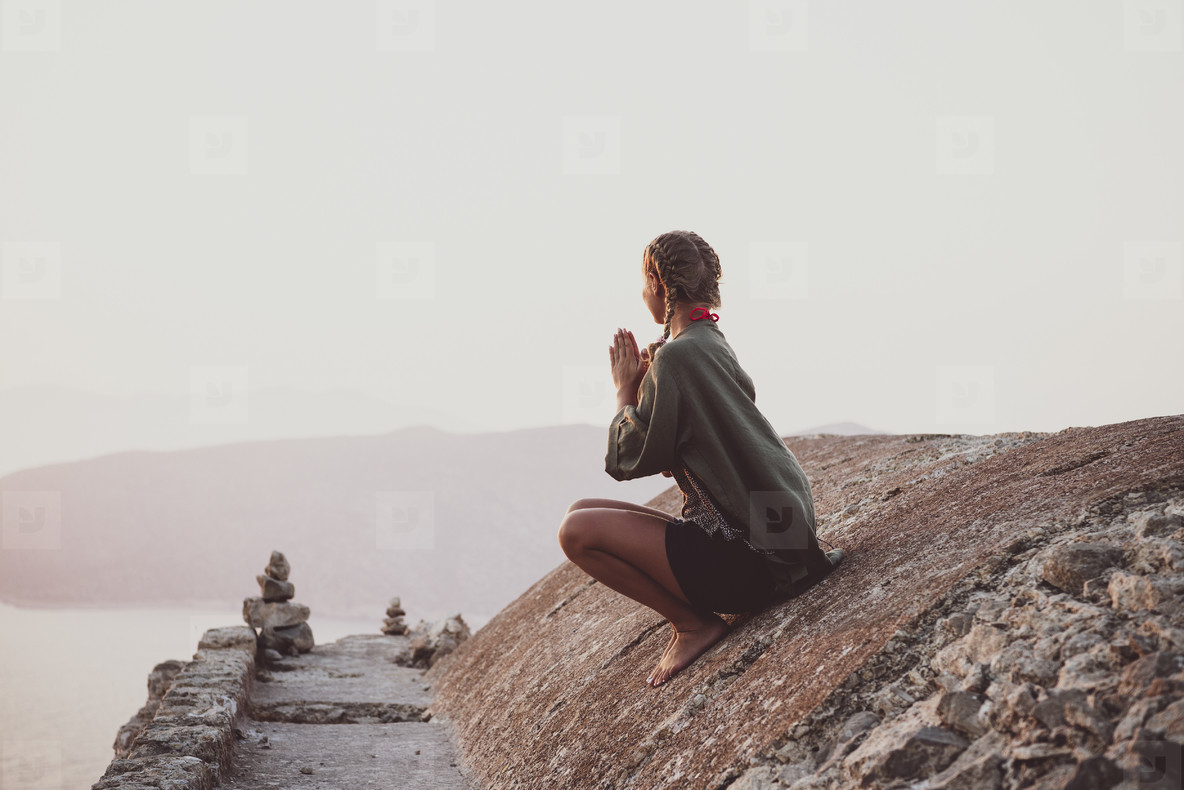 Woman sitting and meditating on stones in Monolithos  Rhodes  Greece