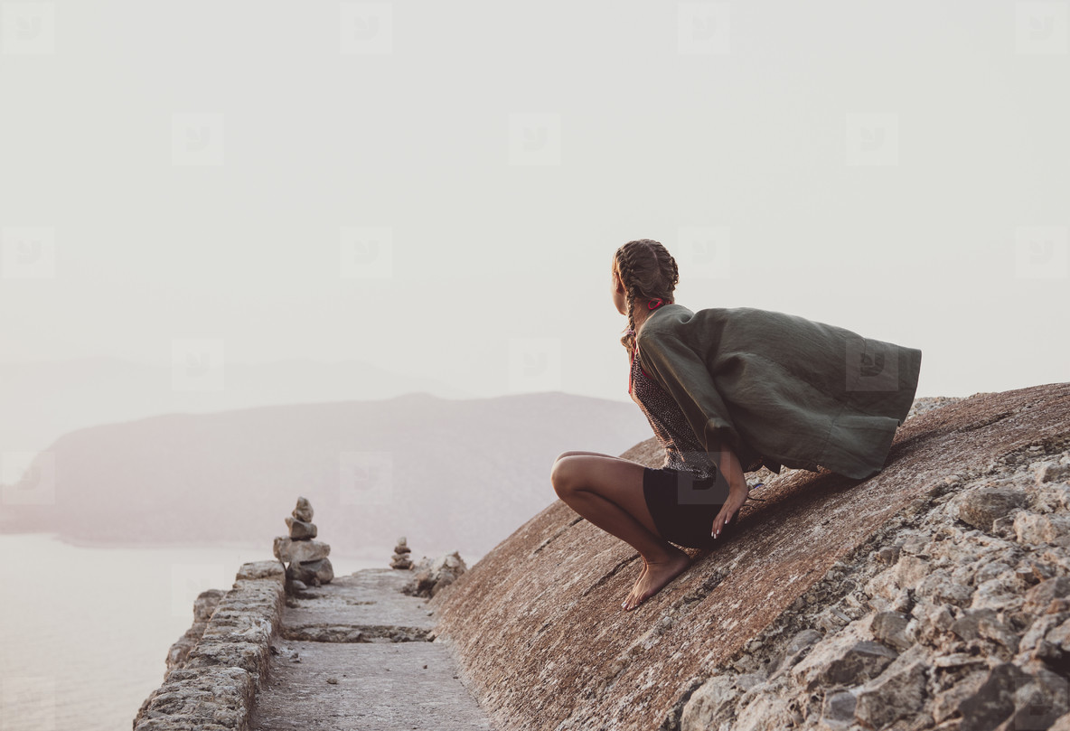 Woman sitting and looking at horizon in Monolithos  Rhodes  Greece