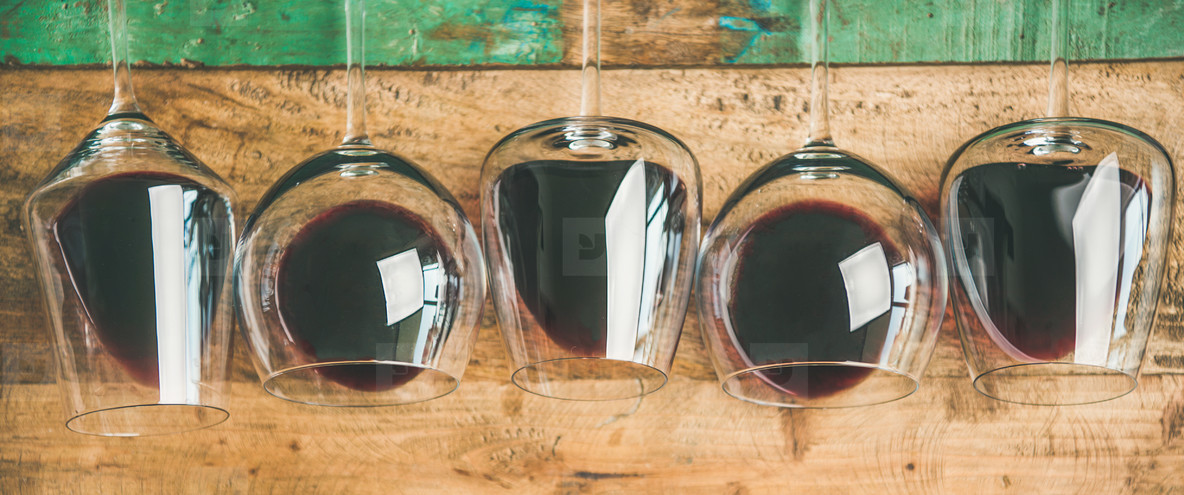 Red wine in glasses over rustic wooden background
