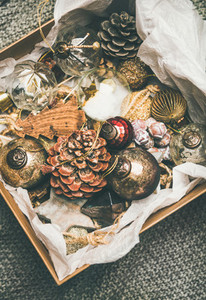 Christmas tree decoration toys and pine cones in wooden box