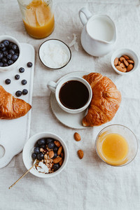 Top view of breakfast table with coffee croissant granola nuts berries and milk Flat lay healthy eating concept