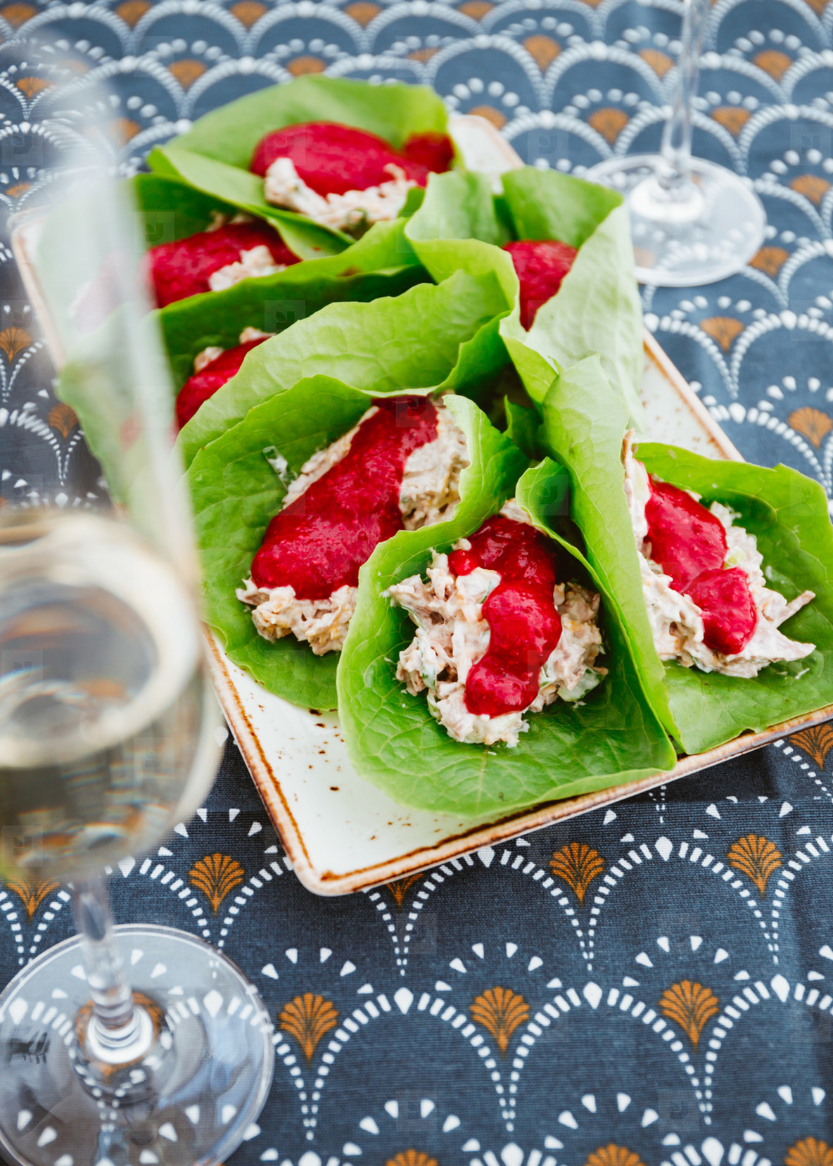 Thanksgiving appetizers are made from turkey leftover in lettuce leaves with cranberry sauce on a festive table