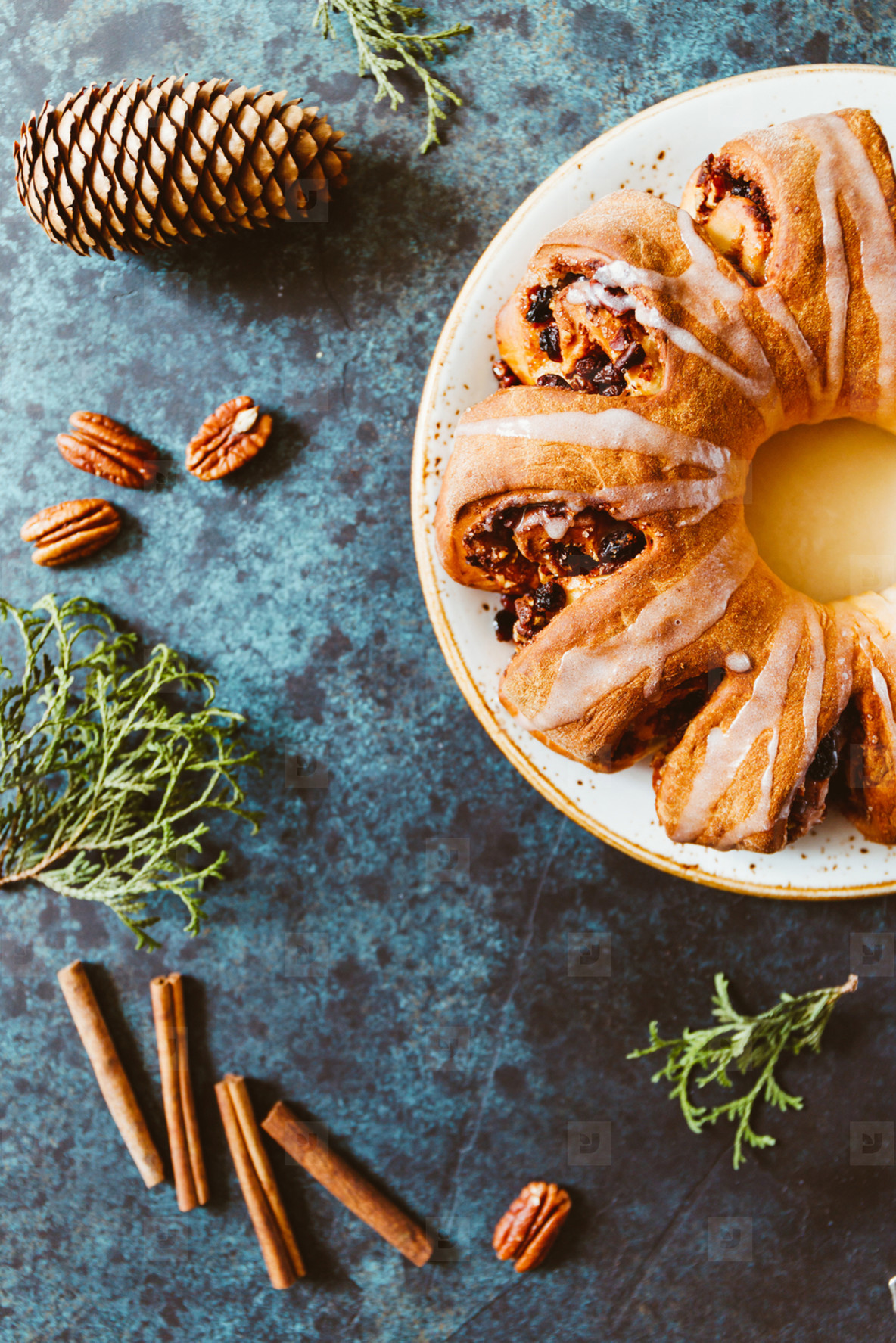 Creative flat lay  top view of Swedish tea ring Christmas cake with cinnamon  pecans and raisins on a blue background  The concept of cozy winter Holidays and homemade bakery